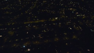 AX123_174 - 6K stock footage aerial video of a reverse view of residential neighborhoods at Night in North Bellmore, New York