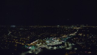 AX123_175 - 6K stock footage aerial video pan across suburban neighborhoods and a strip mall at Night in Wantagh, New York