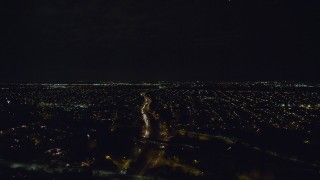 AX123_177 - 6K stock footage aerial video fly over freeway to approach neighborhoods in Massapequa at Night in New York