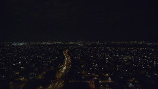 AX123_178 - 6K stock footage aerial video follow Southern State Parkway through Massapequa at Night in New York