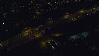 AX123_180 - 6K stock footage aerial video track a car on Southern State Parkway at Night in Massapequa, New York