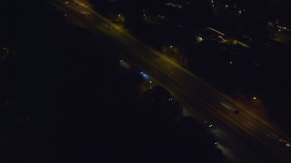 AX123_181 - 6K stock footage aerial video track a car at Night on Southern State Parkway in Massapequa, New York