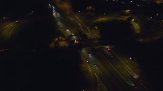 AX123_182 - 6K stock footage aerial video of a reverse view of light traffic on Southern State Parkway in Massapequa, New York at night