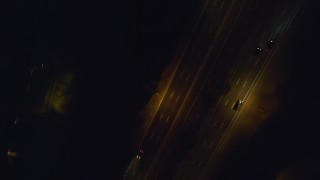 AX123_185 - 6K stock footage aerial video of a bird's eye view of cars on a freeway at Night in Massapequa, New York