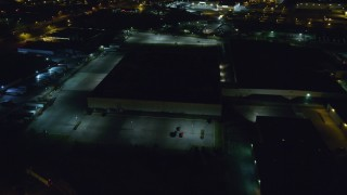 AX123_189 - 6K stock footage aerial video approach dark warehouse at Night in Farmingdale, New York