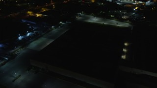 AX123_189E - 5.5K stock footage aerial video approach dark warehouse at Night in Farmingdale, New York