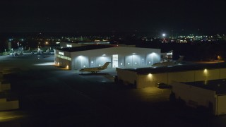 AX123_191 - 6K stock footage aerial video of civilian jets parked outside a hangar at Night at Republic Airport in Farmingdale, New York