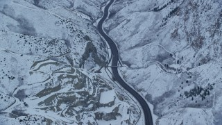 AX124_027 - 6K stock footage aerial video of a snowy mountain highway through Wasatch Range at Sunrise in Utah