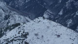 AX124_031 - 6K stock footage aerial video orbit snowy top of Grandeur Peak in Winter at Sunrise in Utah