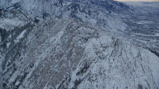 AX124_044 - 6K stock footage aerial video approach snowy summit of Mount Olympus at winter sunrise in Utah