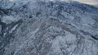 AX124_045 - 6K stock footage aerial video of approaching the top of Mount Olympus with snow at winter sunrise in Utah