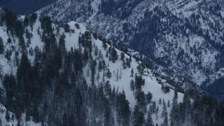 AX124_048 - 6K stock footage aerial video orbit snowy slope of Mount Olympus at winter sunrise in Utah