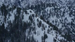AX124_049 - 6K stock footage aerial video orbit snowy slope of Mount Olympus at sunrise in winter, Utah
