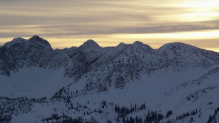 AX124_055 - 6K stock footage aerial video of snowy mountain peaks in the Wasatch Range at sunrise, Utah