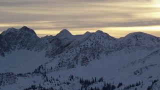 AX124_056 - 6K stock footage aerial video of snowy Wasatch Range mountain peaks at sunrise in winter, Utah