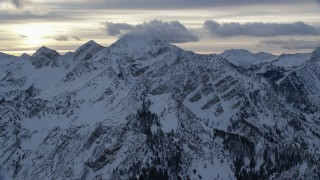 AX124_057 - 6K stock footage aerial video approach Wasatch Range mountains with winter snow at sunrise in Utah