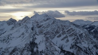 AX124_058 - 6K stock footage aerial video of Wasatch Range mountain peaks with winter snow at sunrise in Utah