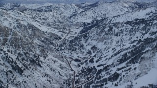 AX124_070 - 6K stock footage aerial video orbit roads and small town of Snowbird in winter at sunrise in Utah