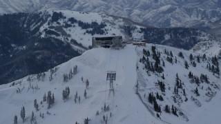 AX124_073 - 6K stock footage aerial video orbit Snowbird Ski Resort ski lifts with winter snow at sunrise in Utah
