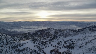 AX124_078 - 6K stock footage aerial video of orbiting snowy Wasatch Range mountains and sunrise in winter, Utah