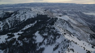 AX124_081 - 6K stock footage aerial video of flying over a snowy ridge toward Mount Wolverine at sunrise in Utah