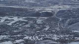 AX124_092 - 6K stock footage aerial video orbit small town neighborhoods with winter snow at sunrise in Park City, Utah