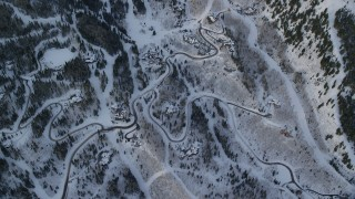 AX124_096 - 6K stock footage aerial video of a bird's eye of mountain roads and homes with snow at sunrise in Park City, Utah