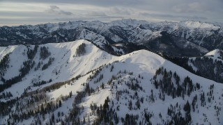 AX124_100 - 6K stock footage aerial video orbit snowy mountains at sunrise in the Wasatch Range of Utah