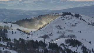 AX124_102 - 6K stock footage aerial video of snowdrifts blowing off a mountain at sunrise in the Wasatch Range, Utah