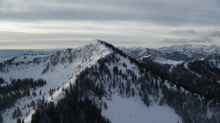 AX124_119 - 6K stock footage aerial video approach summit of snowy Wasatch Range's Clayton Peak at sunrise in Utah