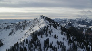 AX124_120 - 6K stock footage aerial video approach top of wintery Clayton Peak at sunrise in the Wasatch Range, Utah