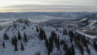 AX124_123 - 6K stock footage aerial video fly over Clayton Peak with winter snow and reveal valley at sunrise in the Wasatch Range, Utah