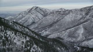 AX124_164 - 6K stock footage aerial video approach Grandeur Peak in the wintery Wasatch Range at sunrise, Utah