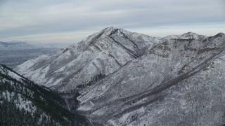 AX124_165 - 6K stock footage aerial video approach snowy Grandeur Peak in winter at sunrise, Utah