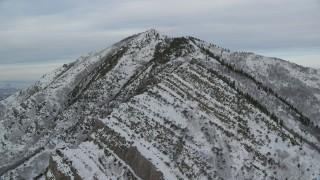 AX124_170 - 6K stock footage aerial video of approaching snowy Grandeur Peak in the Wasatch Range at sunrise, Utah