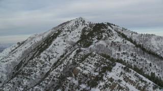AX124_171 - 6K stock footage aerial video approach summit of Grandeur Peak with winter snow at sunrise in Wasatch Range, Utah
