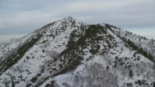 AX124_172 - 6K stock footage aerial video of approaching top of Grandeur Peak with light snow at sunrise in Utah