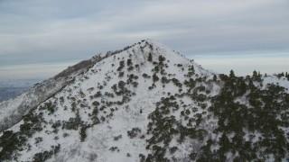 AX124_173 - 6K stock footage aerial video fly to snowy summit of Utah's Grandeur Peak at sunrise