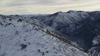 AX124_176 - 6K stock footage aerial video orbit summit of Grandeur Peak with winter snow at sunrise in Utah