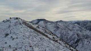 AX124_177 - 6K stock footage aerial video orbiting the top of Grandeur Peak with winter snow at sunrise in Wasatch Range, Utah