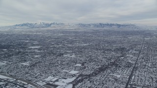 AX124_179 - 6K stock footage aerial video of winter snow on Salt Lake City suburbs and Oquirrh Mountains at sunrise in Utah