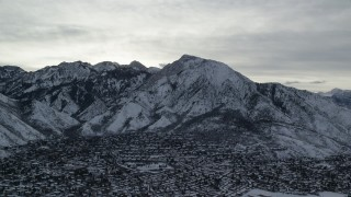 AX124_183 - 6K stock footage aerial video of winter snow on Mount Olympus and Salt Lake City suburbs at sunrise in Utah