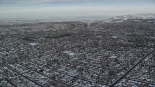 AX124_190 - 6K stock footage aerial video fly over suburbs with winter snow to approach Downtown Salt Lake City at sunrise in Utah