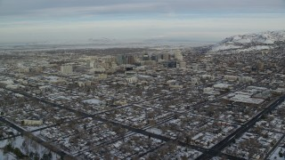 AX124_193 - 6K stock footage aerial video approach Downtown Salt Lake City with winter snow at sunrise in Utah