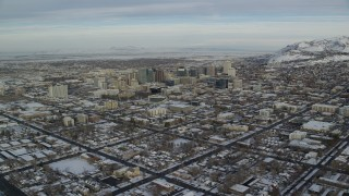 AX124_194 - 6K stock footage aerial video approach Downtown Salt Lake City buildings in winter snow at sunrise in Utah