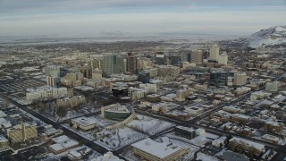 AX124_195 - 6K stock footage aerial video approach wintery Downtown Salt Lake City, Utah with snow at sunrise