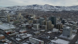 AX124_209 - 6K stock footage aerial video of circling snowy Downtown Salt Lake City in winter at sunrise in Utah