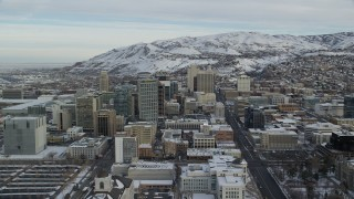 AX124_213 - 6K stock footage aerial video approach buildings in Downtown Salt Lake City with snow at sunrise in Utah