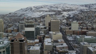 AX124_215 - 6K stock footage aerial video approach Downtown Salt Lake City buildings and Utah State Capitol at sunrise in winter