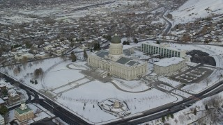 AX124_218 - 6K stock footage aerial video orbit snowy grounds of Utah State Capitol in winter at sunrise in Salt Lake City